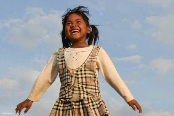 Petite fille souriante avec le ciel en fond