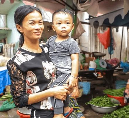 Une mère vietnamienne portant son jeune enfant dans les bras