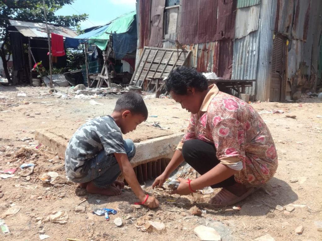Une mère et son fils participent au nettoyage du site de drainage