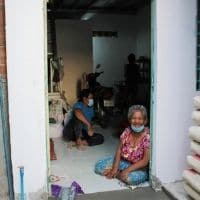 Mme P.V à l'entrée de sa maison rénovée