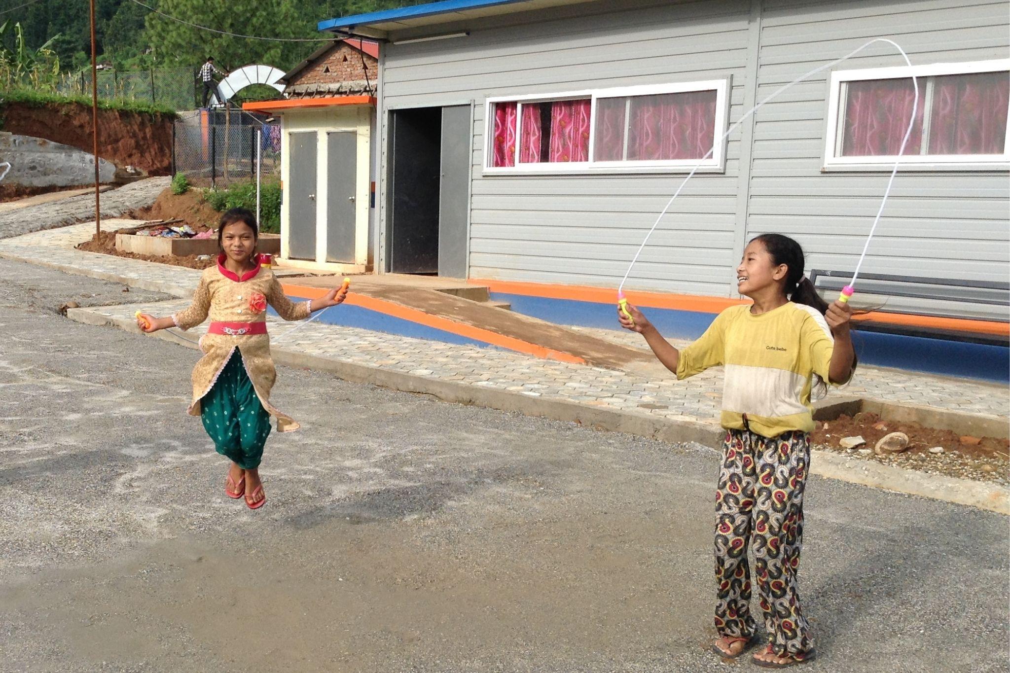 Jeunes filles de l'ethnie Chepang qui jouent devant leur nouveau foyer